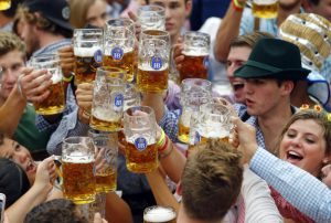 People celebrate the opening of the 182. Oktoberfest beer festival in Munich, southern Germany, Saturday, Sept. 19, 2015. The world's largest beer festival will be held from Sept. 19 to Oct. 4, 2015. (AP Photo/Matthias Schrader)